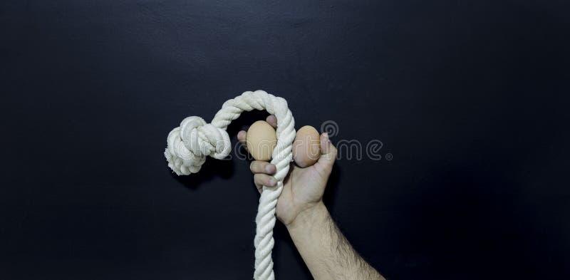 Bemannen Sie das Halten des Seils und zwei Eier erektile Dysfunktion zeigend stockfotografie