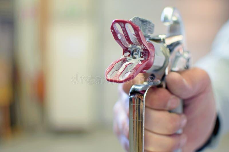 Bemannen Sie das Halten einer benutzten luftlosen FarbenFarbspritzpistole lizenzfreie stockfotografie