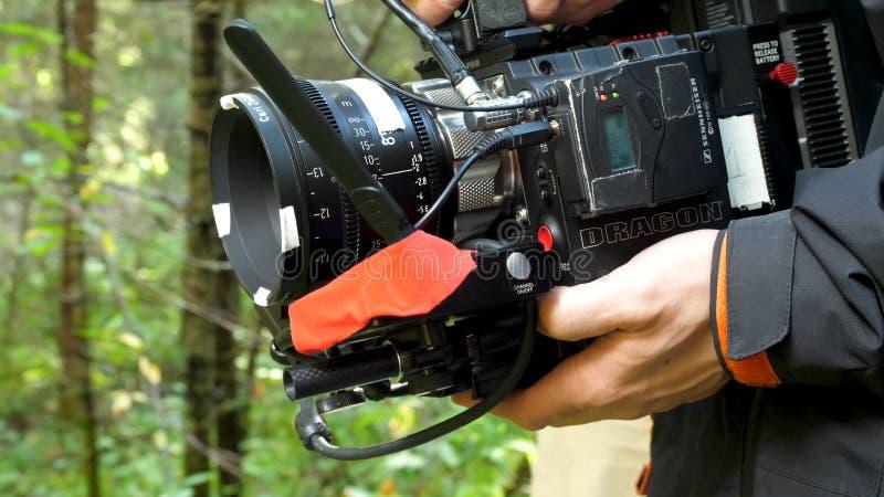 Bemannen Sie das Halten einer Kamera, die im Wald einen Film in der Waldteuren Kamera für Film filmt stockfoto