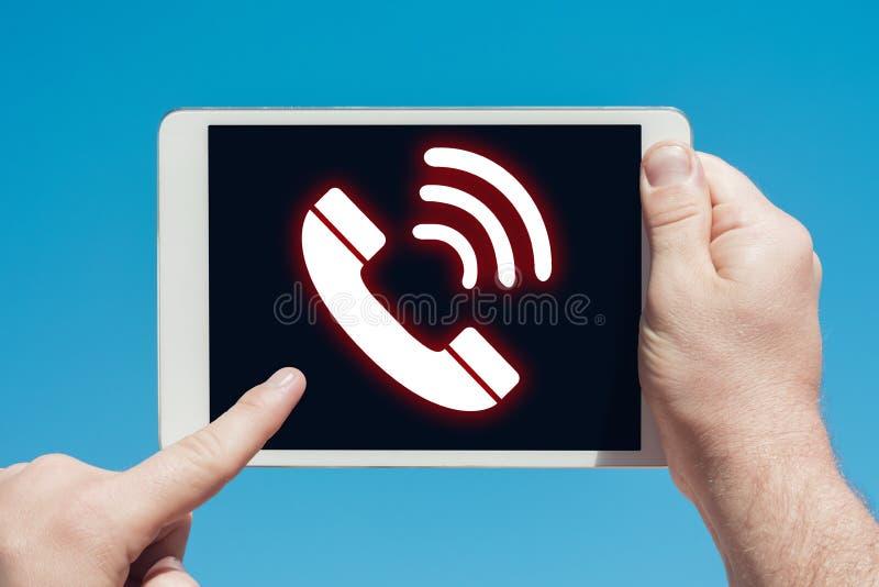 Bemannen Sie das Halten eines Tablettengerätes mit Telefonikone stockfoto