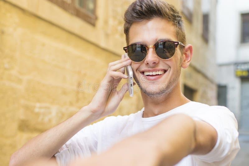 Bemannen Sie das Halten seiner Hand, die am Telefon spricht stockfoto