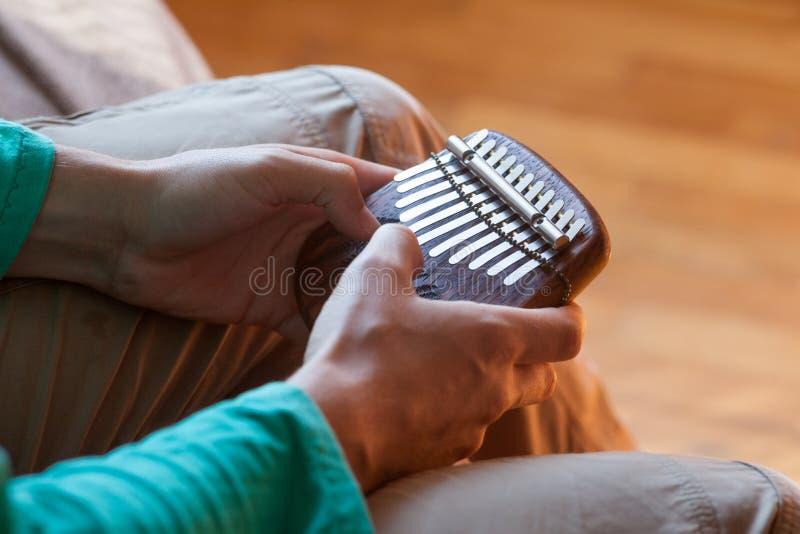 Bemannen Sie das Halten traditionellen afrikanischen Musikinstrument kalimba in ein ` s Händen Mann, der auf dem kalimba spielt lizenzfreie stockfotografie