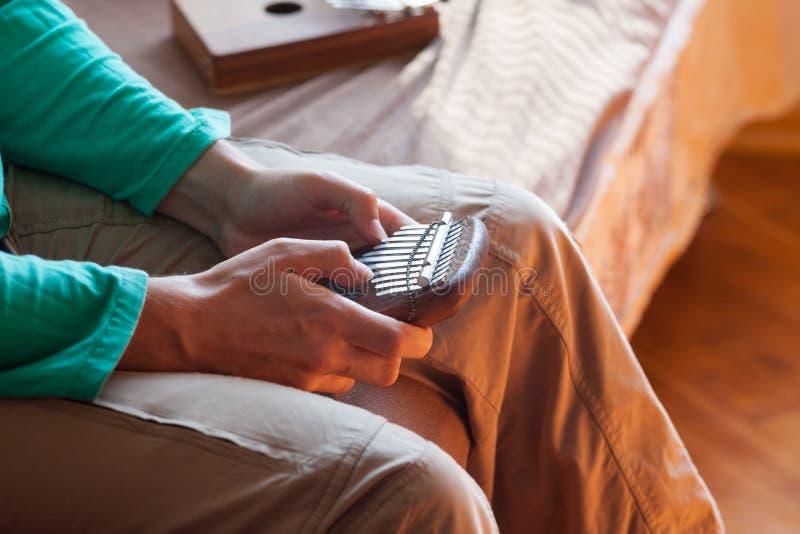 Bemannen Sie das Halten traditionellen afrikanischen Musikinstrument kalimba in ein ` s Händen Mann, der auf kleinem kalimba spie lizenzfreie stockfotos