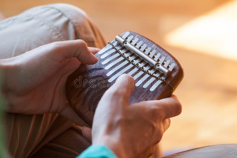 Bemannen Sie das Halten traditionellen afrikanischen Musikinstrument kalimba in ein ` s Händen Bemannen Sie das Spielen auf einer lizenzfreie stockfotos