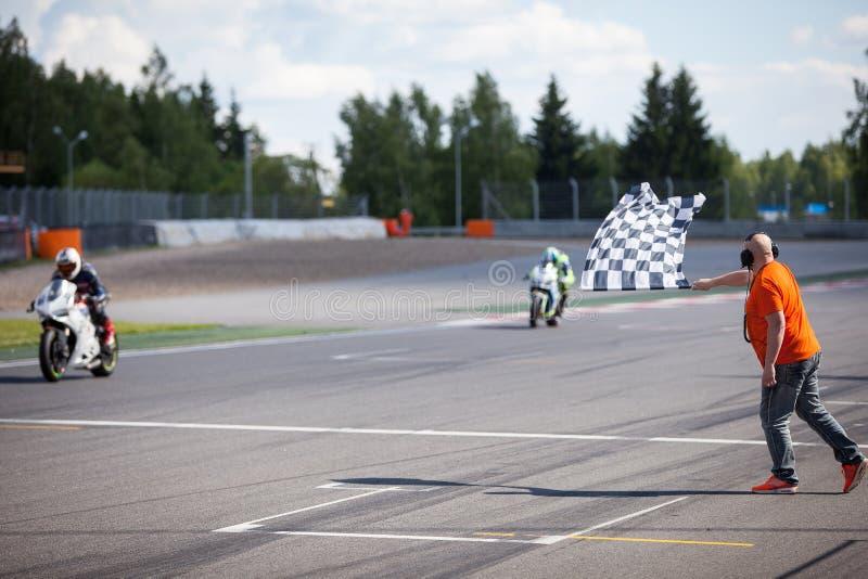 Bemannen Sie das Halten und das Wellenartig bewegen der Zielflagge am Ende des Rennens stockfotografie