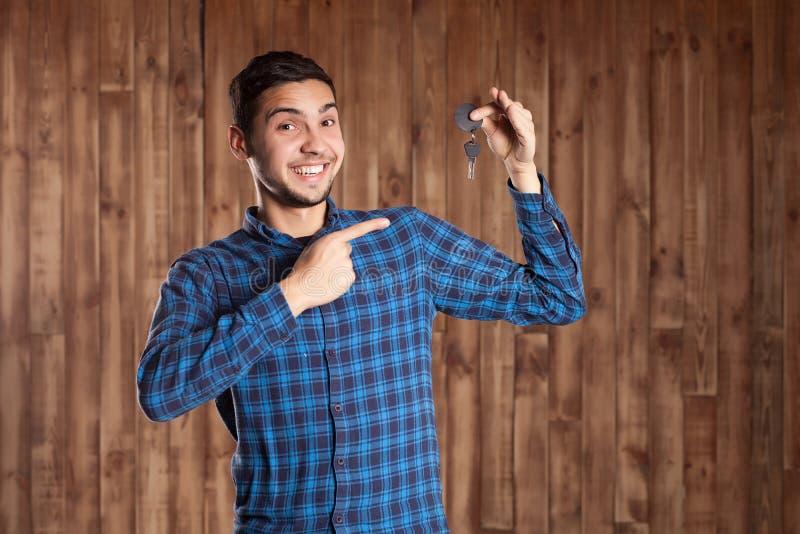 Bemannen Sie das Halten von Autoschlüsseln auf einem braunen Hintergrund lizenzfreies stockbild