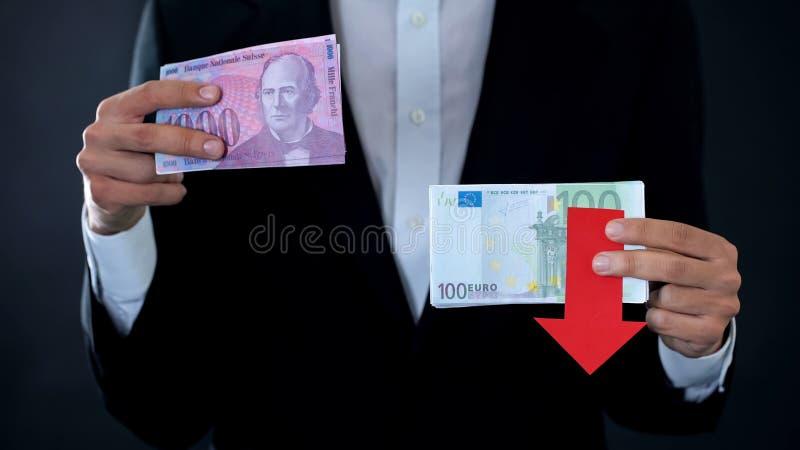 Bemannen Sie das Halten von Banknoten, der Euro, der im Verhältnis zu Schweizer Franken, Finanzprognose fällt lizenzfreie stockfotografie