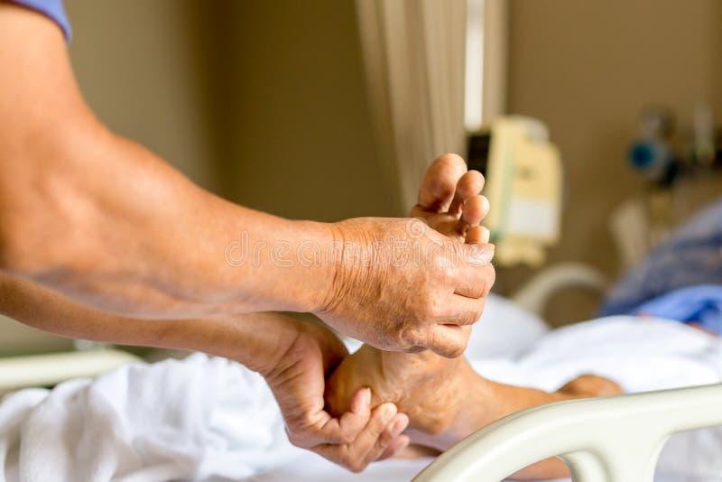 Bemannen Sie das Handeln des Behandlungspatienten des körperlichen Therapeuten, der einen Fuß mas gibt lizenzfreie stockbilder