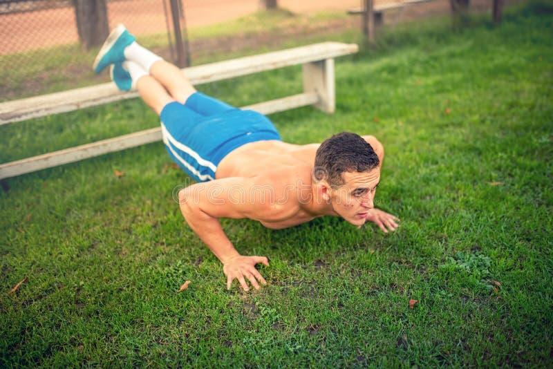 Bemannen Sie das Handeln von Liegestützen im Park, im Bodybuilding und im Training Eignungskonzept mit hemdlosem Mann draußen, tu lizenzfreie stockfotografie