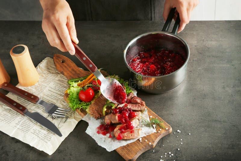 Bemannen Sie das Hinzufügen der frisch gekochten Preiselbeersoße geschnittenem Steak stockfotos