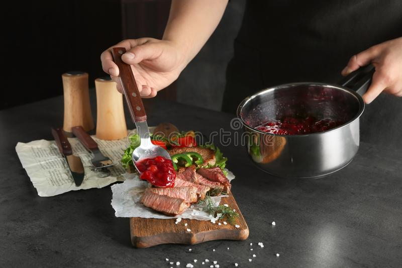 Bemannen Sie das Hinzufügen der frisch gekochten Preiselbeersoße geschnittenem Steak stockbild