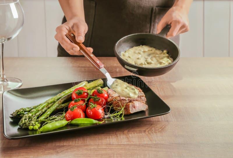 Bemannen Sie das Hinzufügen der Soße geschnittenem Steak mit Gemüse lizenzfreie stockbilder