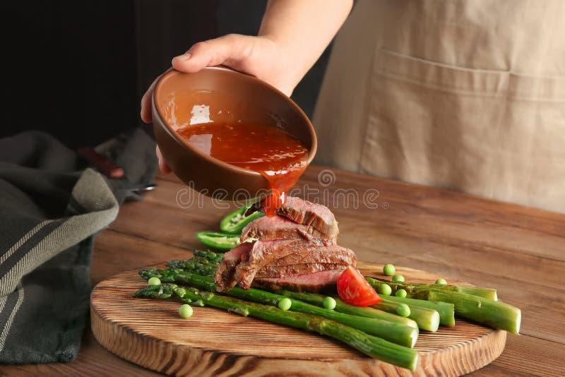Bemannen Sie das Hinzufügen der Soße geschnittenem Steak mit Spargel lizenzfreie stockbilder