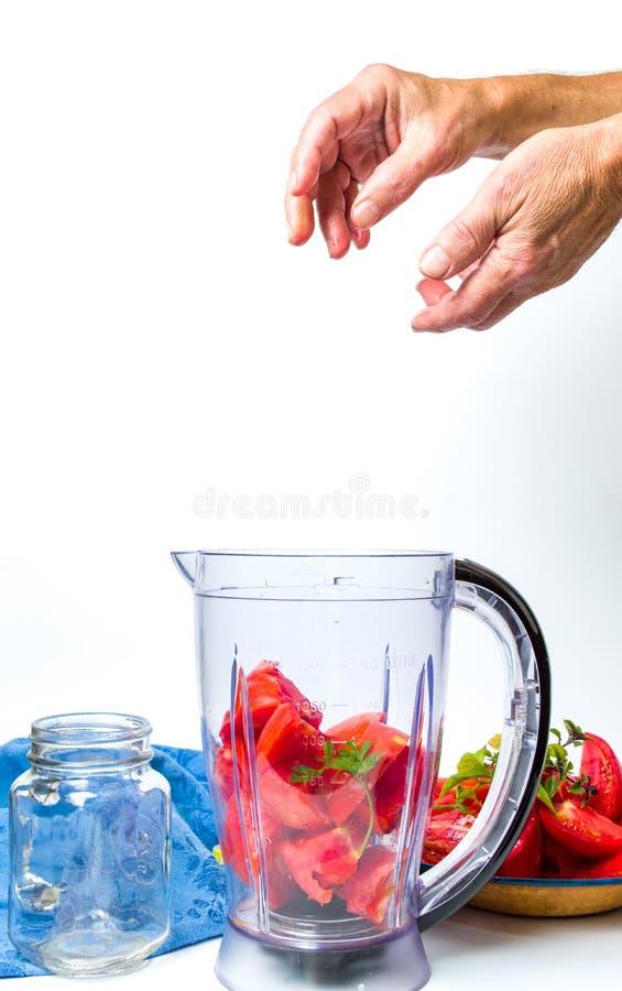 Bemannen Sie das Hinzufügen von Tomatenscheiben in einer Mischmaschine für einen Smoothie lizenzfreie stockfotos