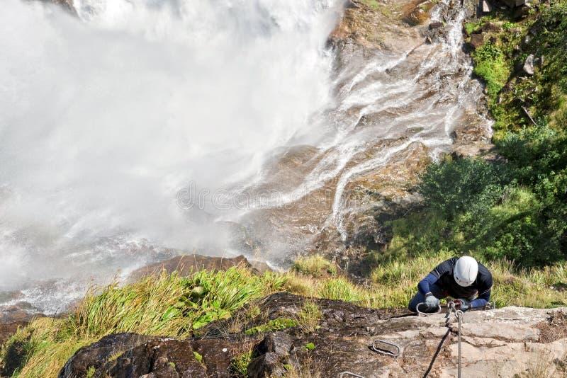 Bemannen Sie das Klettern auf a über ferrata nahe einem Wasserfall lizenzfreies stockfoto