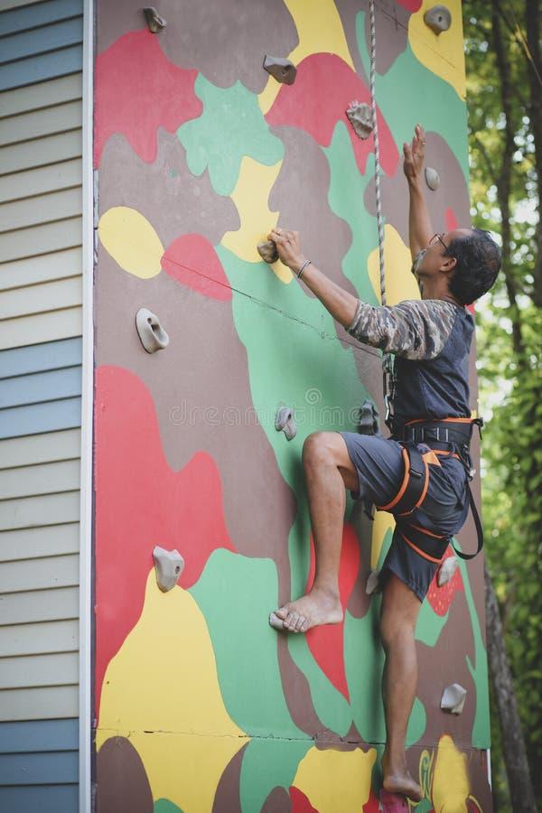 Bemannen Sie das Klettern auf tragendem Sicherheitsgurt der künstlichen Felsenklippe Sui stockfotos