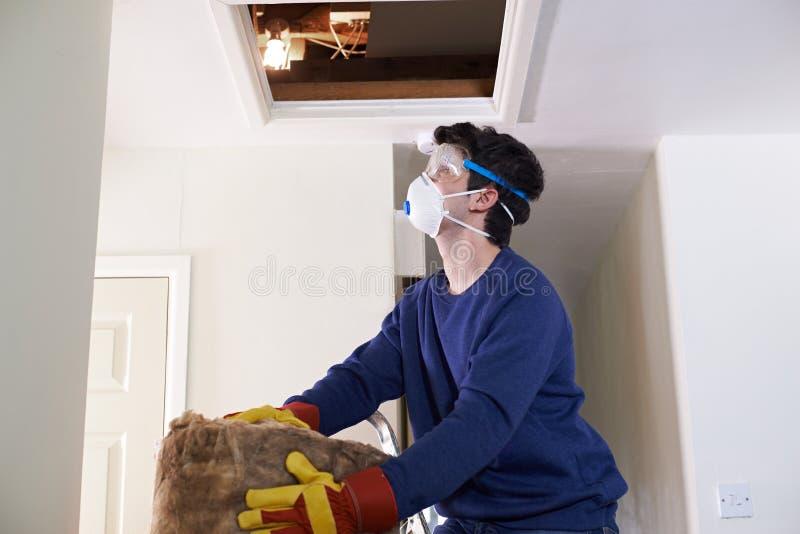 Bemannen Sie das Klettern in Dachboden zum Isolieren von Haus-Dach stockfotos
