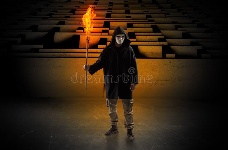Bemannen Sie das Kommen mit brennendem Flambeau vom Labyrinthkonzept lizenzfreie stockfotografie