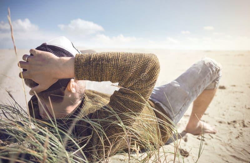 Bemannen Sie das Lügen auf einem Strand in der Nordsee stockfoto