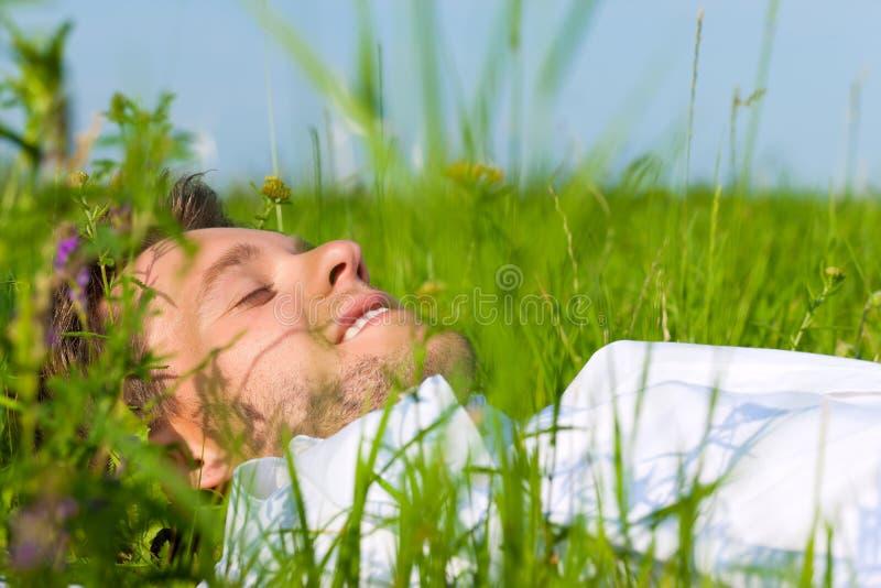 Bemannen Sie das Legen auf einen Rasen und träumt lizenzfreie stockfotografie