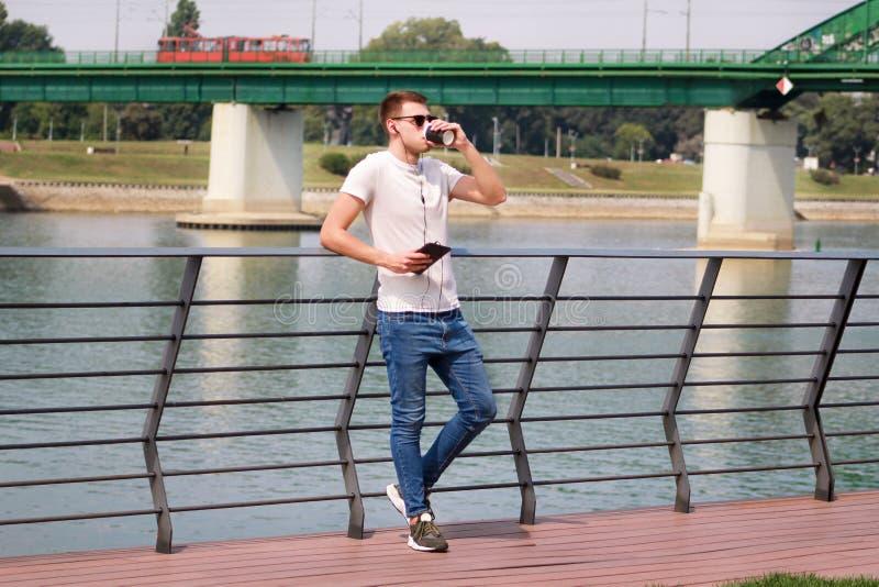 Bemannen Sie das Lehnen auf dem Zaun unter Verwendung der Tablette und Kopfhörer und seine Umgebungen durch den Fluss und den alt lizenzfreie stockfotos
