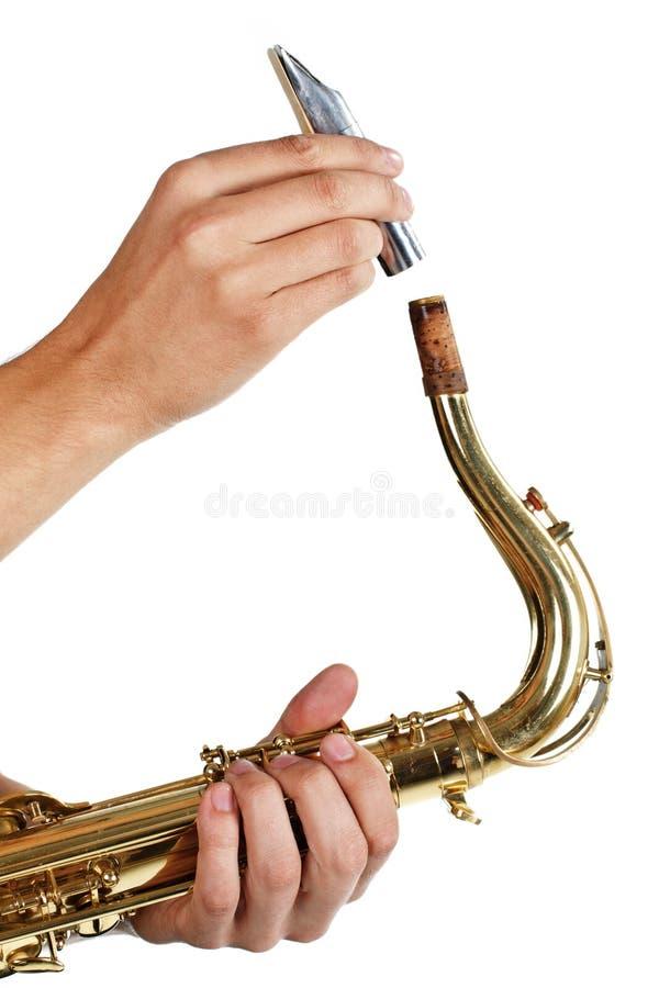 Bemannen Sie das Mundstück auf das Saxophon zurück setzen stockfoto