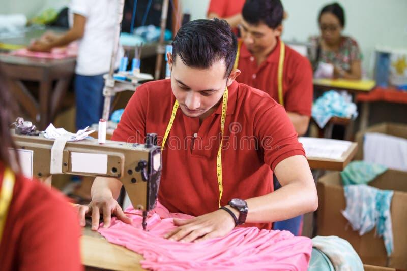 Bemannen Sie das Nähen auf einer Nähmaschine an einer Kleidungsfabrik stockbilder
