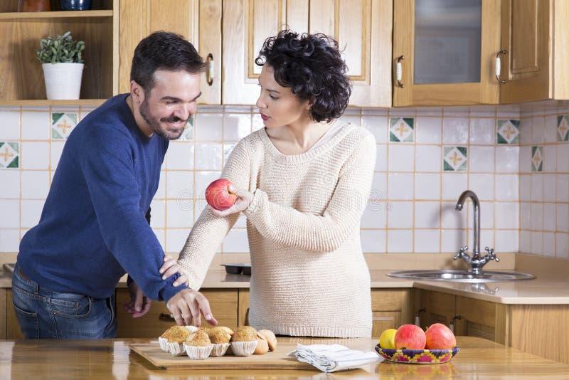 Bemannen Sie das Nehmen des köstlichen kleinen Kuchens während ihre Frau, die ihm eine APP anbietet stockfotografie