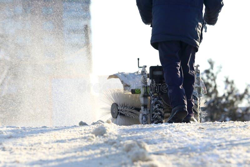 Bemannen Sie das Säubern der Straße von manuellem Special Traktor des Schnees lizenzfreie stockfotografie