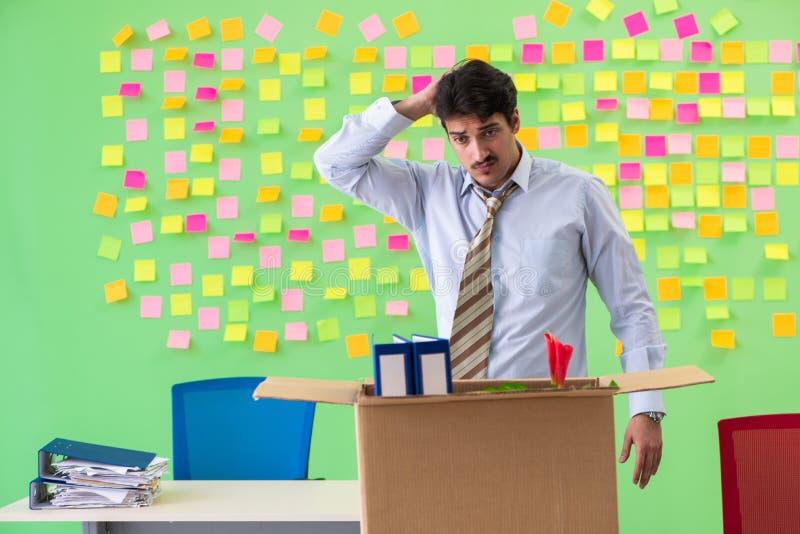 Bemannen Sie das Sammeln seines Materials nach Redundanz im Büro mit Mann stockfoto