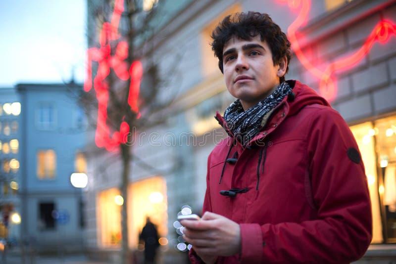 Bemannen Sie das Schauen weg beim Halten des Handys in der Stadt während des Winters stockfotografie