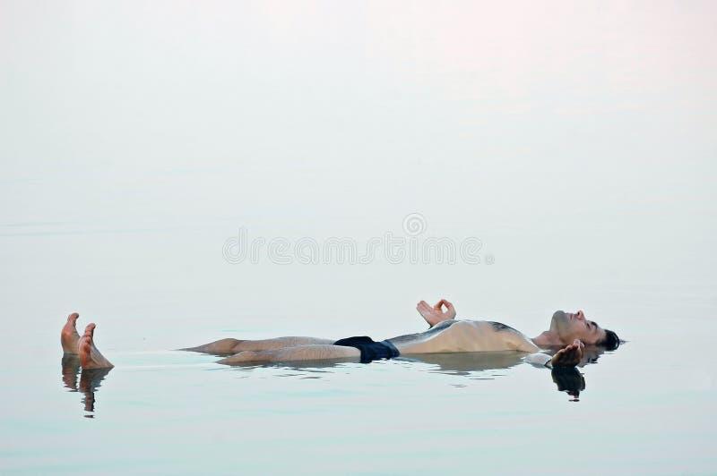 Bemannen Sie das Schwimmen in ein glasiges Wasser von Totem Meer lizenzfreie stockfotografie