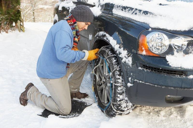 Bemannen Sie das Setzen der Schnee-Ketten auf Reifen des Autos lizenzfreie stockfotos