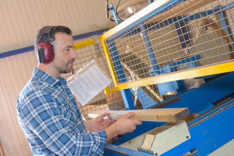 Bemannen Sie das Setzen des Holzes in Maschine lizenzfreie stockfotografie