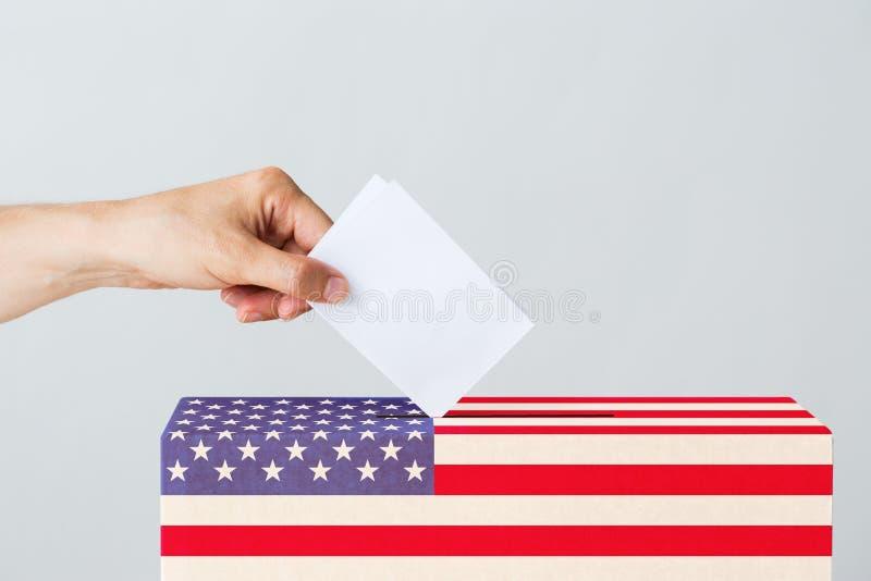 Bemannen Sie das Setzen seiner Abstimmung in Wahlurne auf Wahl stockfotografie