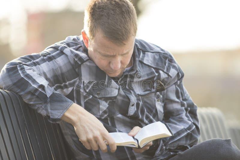 Bemannen Sie das Sitzen auf Bank und das Ablesen der Bibel und das Denken stockbild