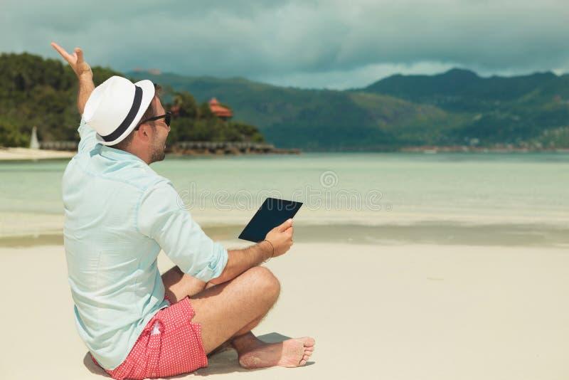 Bemannen Sie das Sitzen auf dem Strand und das Wellenartig bewegen beim Halten eines ipad lizenzfreies stockfoto
