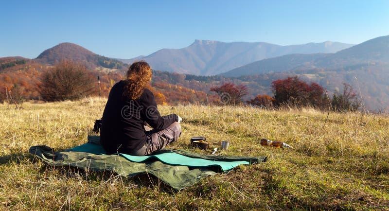 Bemannen Sie das Sitzen auf der Wiese und der herbstlichen Ansicht des Bergs Klak lizenzfreies stockfoto