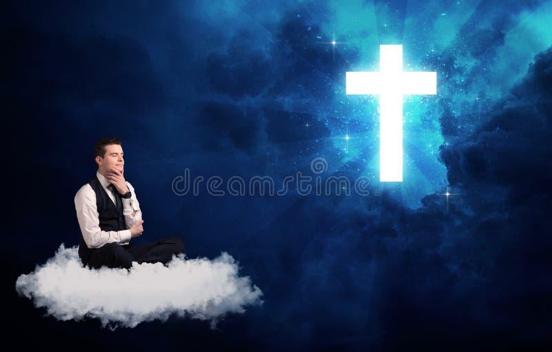 Bemannen Sie das Sitzen auf der Wolke, die an einem Kreuz lokking ist stockfotos