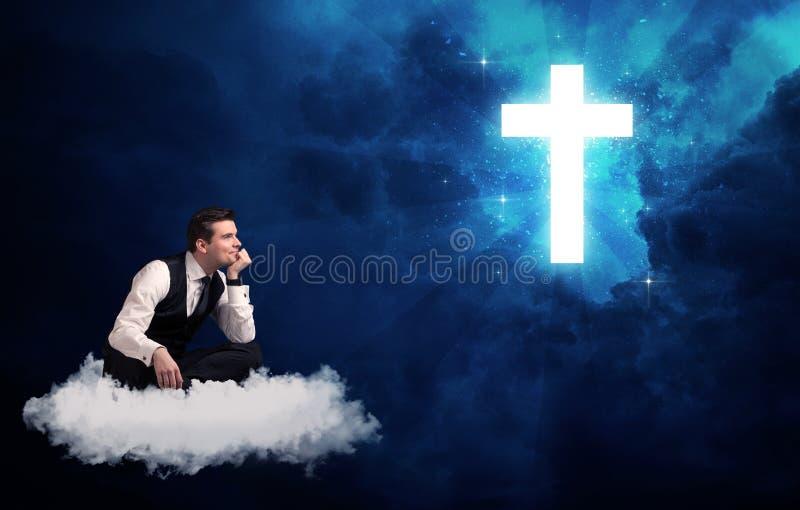 Bemannen Sie das Sitzen auf der Wolke, die an einem Kreuz lokking ist stockfoto