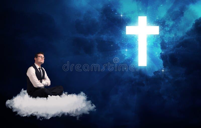 Bemannen Sie das Sitzen auf der Wolke, die an einem Kreuz lokking ist lizenzfreie stockbilder