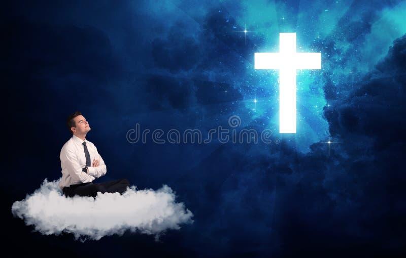 Bemannen Sie das Sitzen auf der Wolke, die an einem Kreuz lokking ist stockbilder