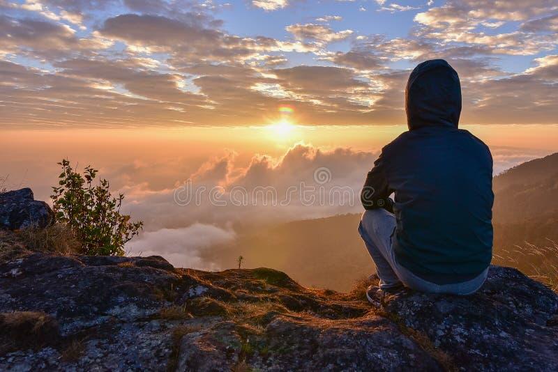 Bemannen Sie das Sitzen auf einem Berg für aufpassende Sonnenaufgangansichten lizenzfreies stockfoto