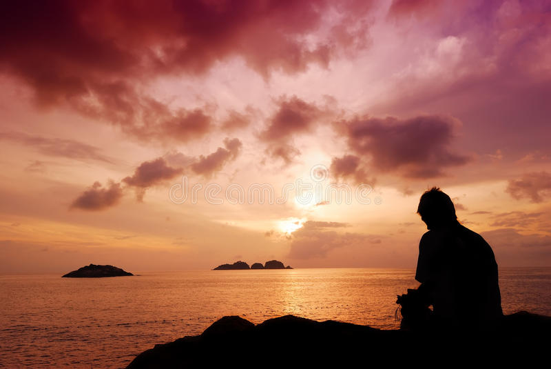 Bemannen Sie das Sitzen auf einem kleinen Felsen, der den schönen Sonnenaufgang aufpasst lizenzfreie stockbilder
