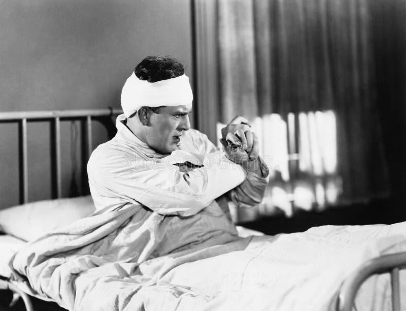 Bemannen Sie das Sitzen auf einem Krankenhausbett, das gefürchtet schaut (alle dargestellten Personen sind nicht längeres lebende stockbilder