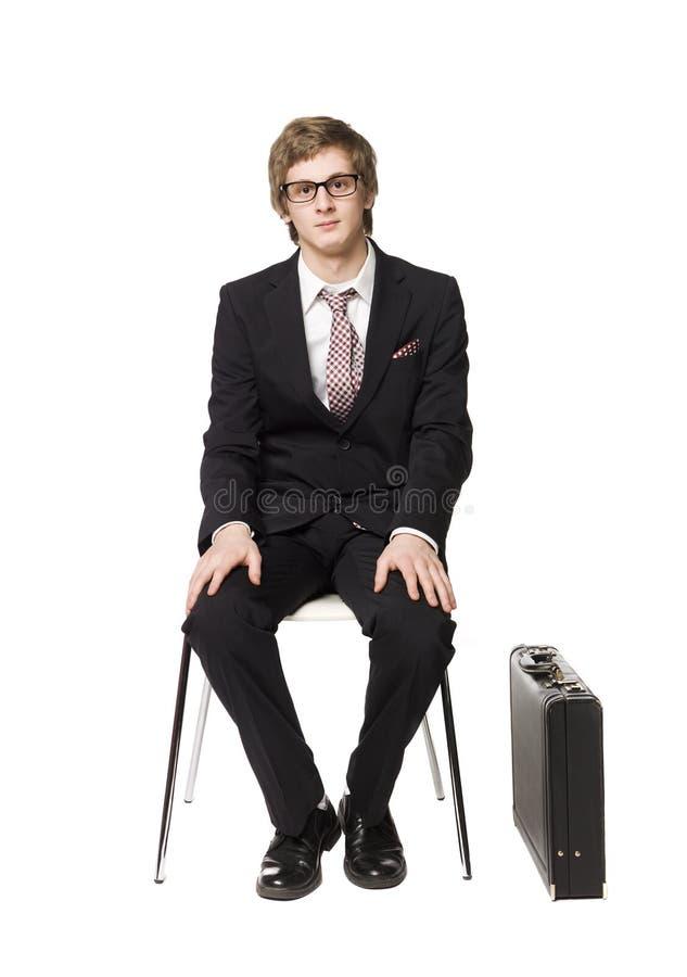 Bemannen Sie das Sitzen auf einem Stuhl stockfoto