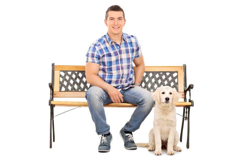Bemannen Sie das Sitzen auf einer Bank mit einem netten Welpen lizenzfreie stockfotografie