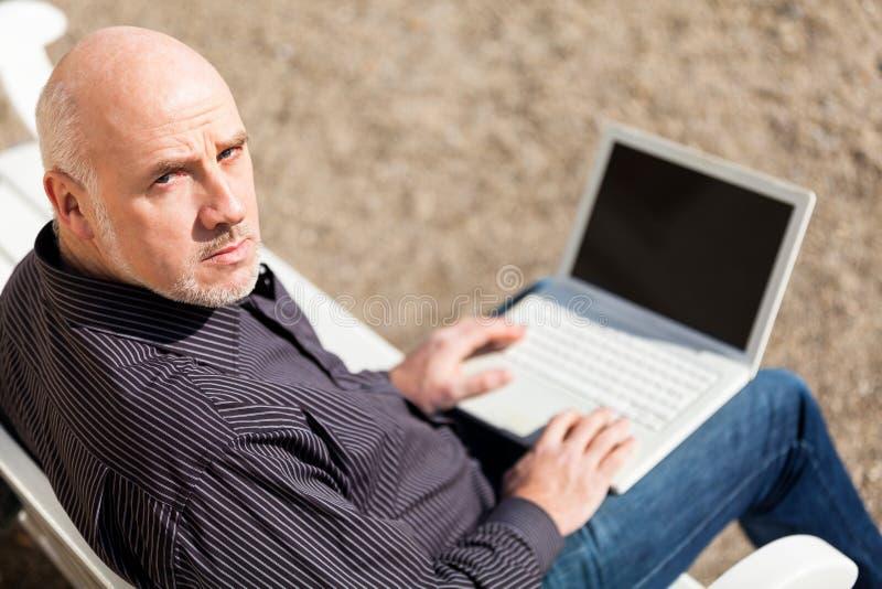 Bemannen Sie das Sitzen auf einer Bank unter Verwendung eines Laptops stockbilder