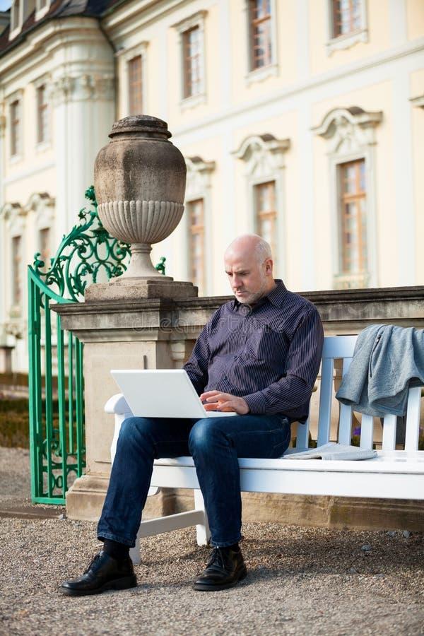Bemannen Sie das Sitzen auf einer Bank unter Verwendung eines Laptops stockfotos