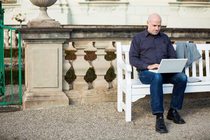 Bemannen Sie das Sitzen auf einer Bank unter Verwendung eines Laptops stockfotografie